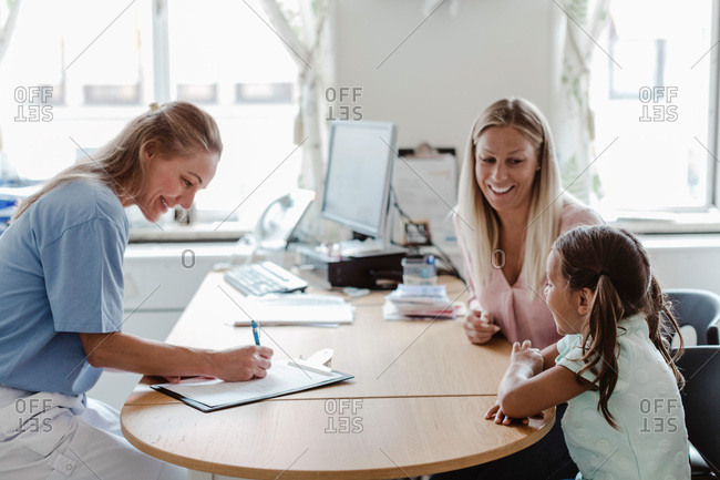 Smiling pediatrician writing prescription while girl sitting with mother at desk in clinic