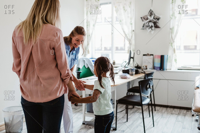 Smiling pediatrician shaking hands with girl while mother standing in doctor's office