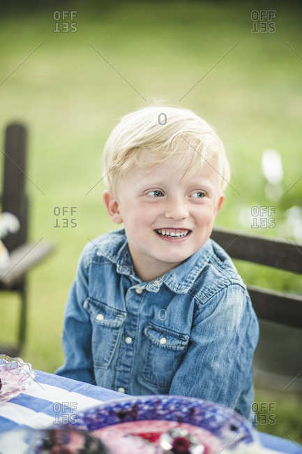 Smiling boy looking away while sitting at table in garden