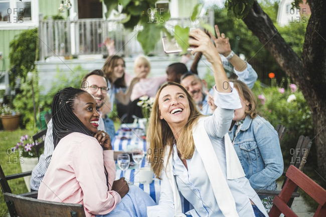 Happy woman taking selfie with friends on smart phone in backyard during garden party