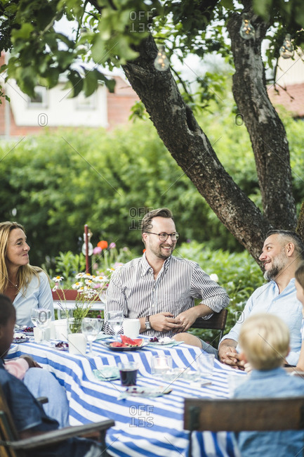 Friends talking while sitting at dining table in garden party during summer weekend