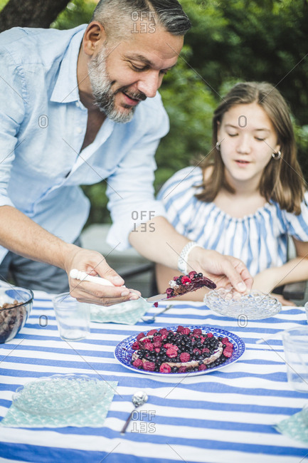 Man serving berry tart to daughter at table in backyard
