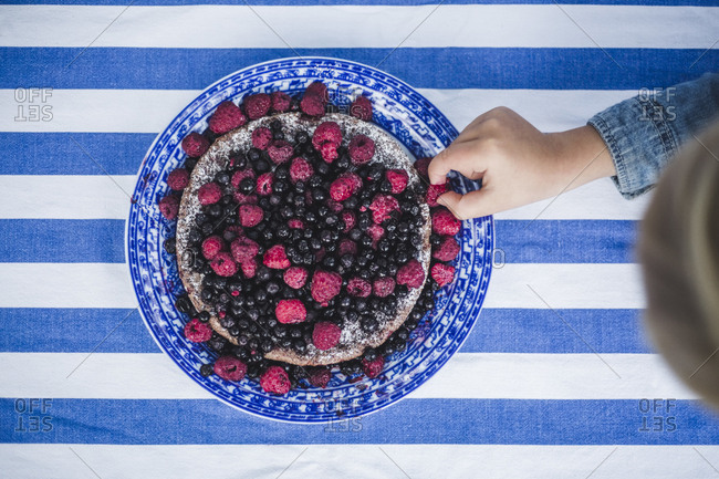 Directly above shot of boy picking up raspberry in tart at table