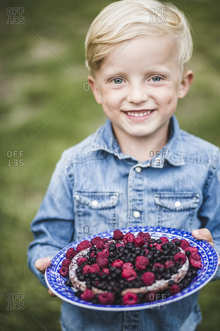 Portrait of smiling boy holding berry tart in garden