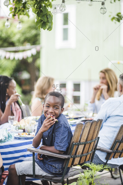Smiling boy eating watermelon while sitting with family in garden party