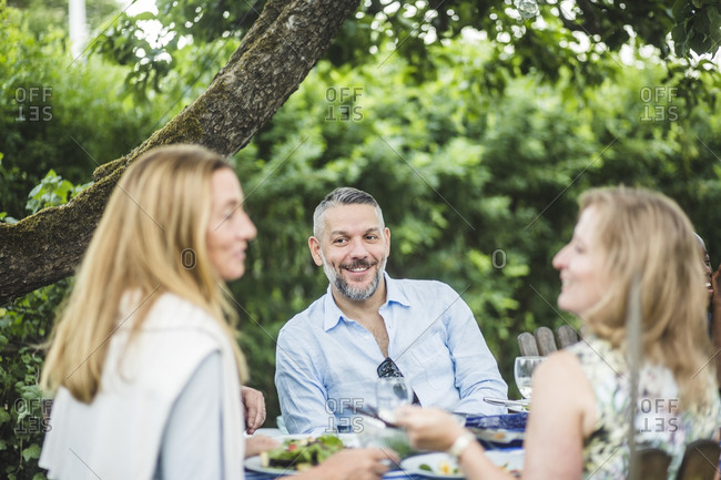 Smiling mature man looking at female friends while enjoying garden party during weekend