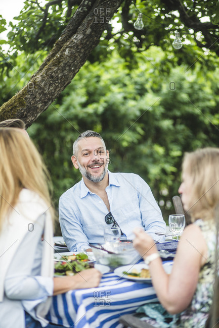 Happy man enjoying with friends at dining table in garden party