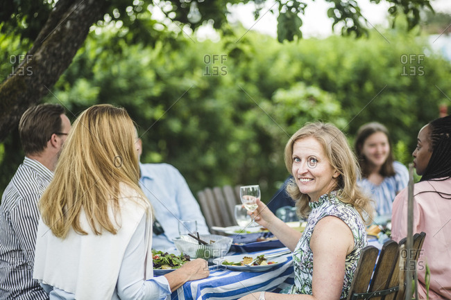 Smiling woman holding wine glass while sitting with friends at garden party