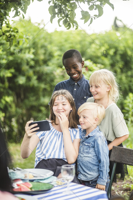 Girl taking selfie with friends on mobile phone in backyard