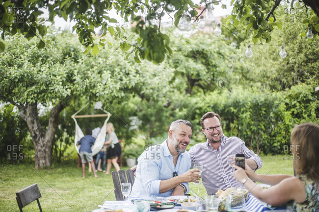 Woman with mobile phone photographing male friends enjoying drinks at garden party