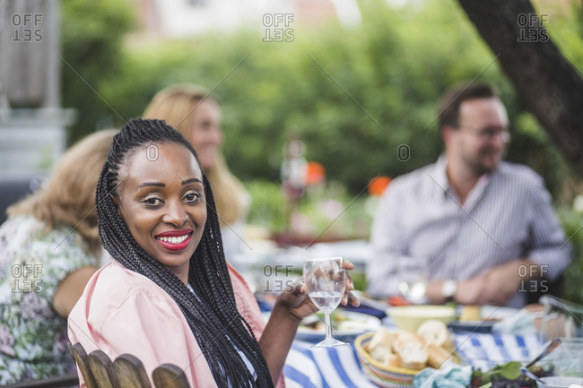 Portrait of smiling woman having wine while sitting with friends at garden party
