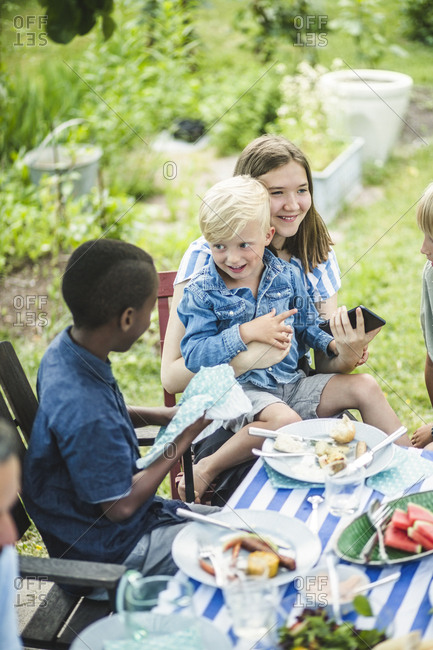 High angle view of friends sitting together at dining table in garden party