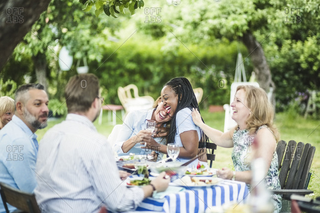 Friends enjoying and having fun while sitting at dining table in garden during summer weekend