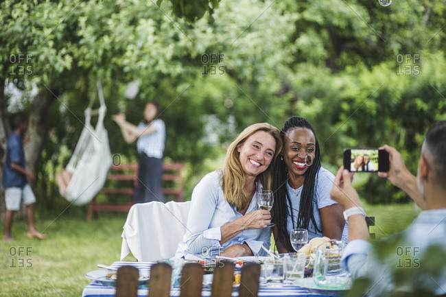 Man photographing friends with wine through mobile phone in garden party