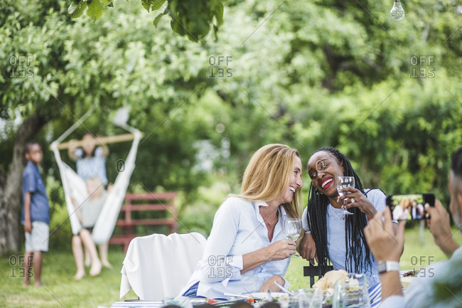 Man with mobile phone photographing smiling women having wine in garden party at weekend