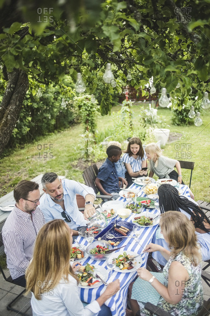 High angle view of friends and family enjoying at dining table in garden party
