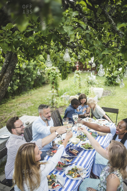 High angle view of friends toasting wineglasses during backyard party in summer