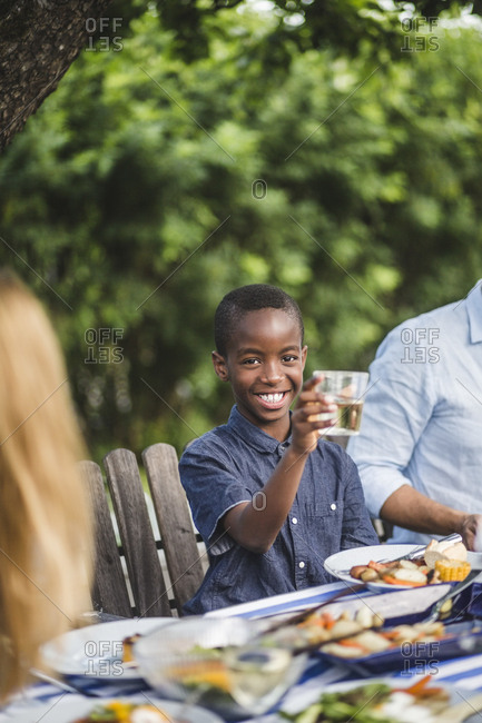 Smiling boy holding drinking glass while sitting with family in backyard during party
