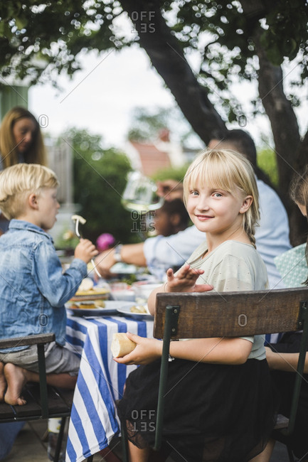 Portrait of smiling girl sitting with friends and family at table in garden party