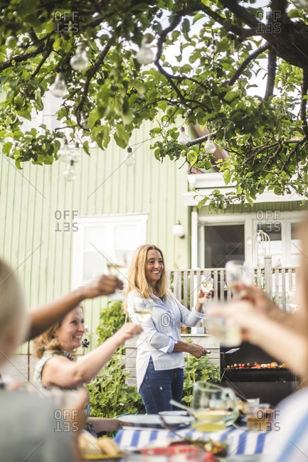 Mature woman preparing food on barbecue while toasting wineglasses with friends at backyard party