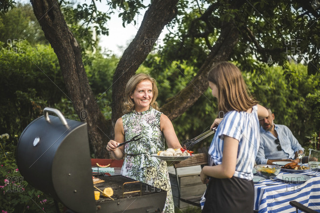 Smiling mother looking at daughter assisting in preparing food at barbecue grill in backyard during weekend party