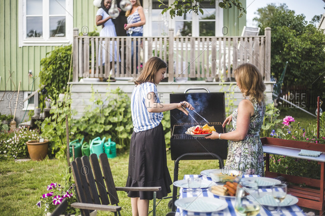 Mother and daughter preparing food on barbecue in backyard party
