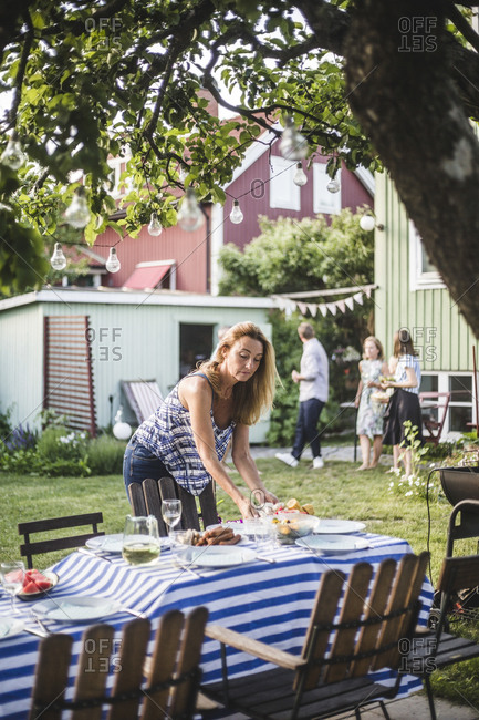 Mature woman arranging food on table in backyard during weekend
