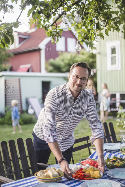 Portrait of mature man placing food plate on table in backyard while preparing for garden party
