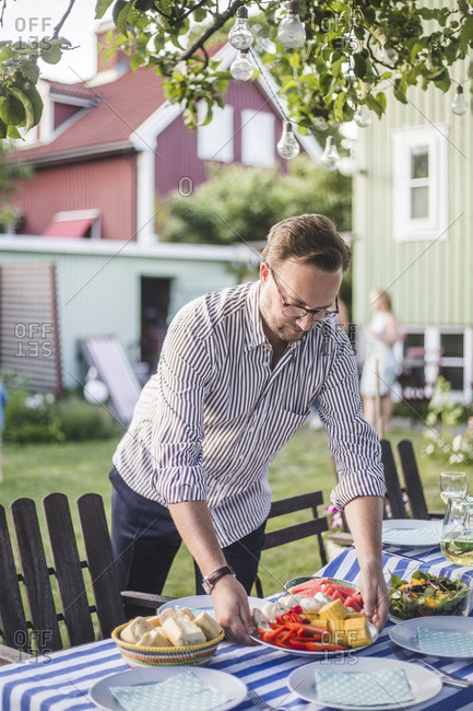 Man arranging food plate on table for garden party in backyard during summer weekend