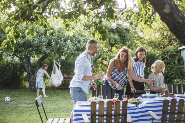 Family arranging food on table for social gathering during summer weekend