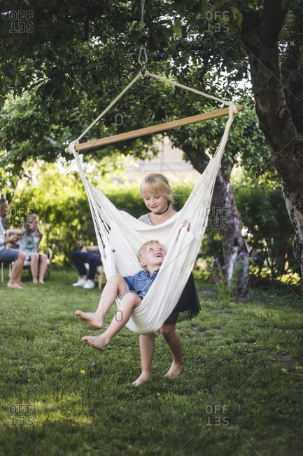 Full length of sister swinging little boy in backyard