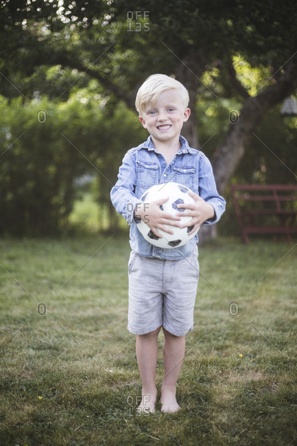 Portrait of cute boy standing while holding football in backyard