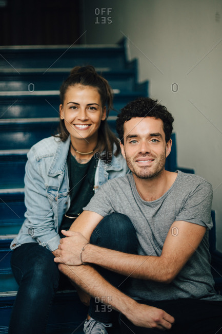 Portrait of smiling couple sitting on steps in apartment