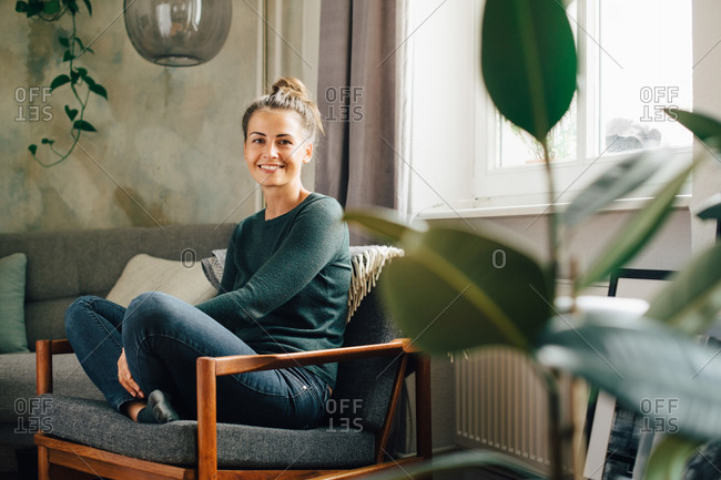 Portrait of smiling woman sitting on armchair at home