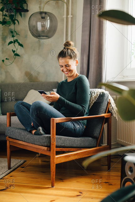 Mid adult woman smiling while using mobile phone on armchair at home
