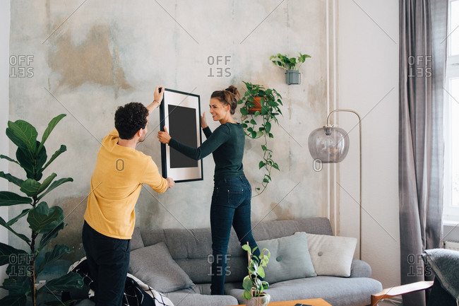 Mid adult man passing picture frame to girlfriend against wall at new home
