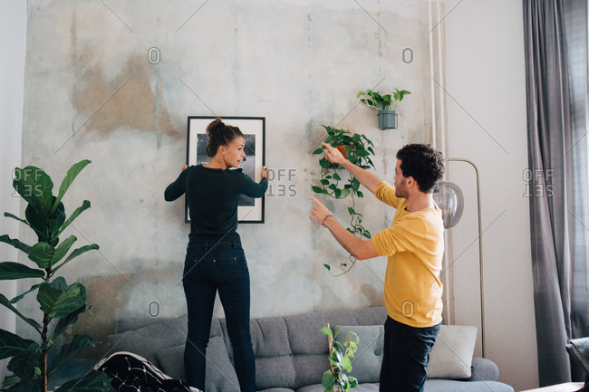 Boyfriend guiding girlfriend in hanging picture frame on wall at new home