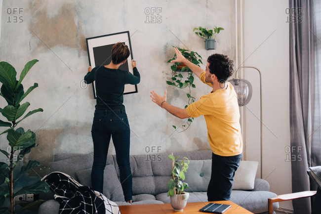 Mid adult man guiding girlfriend in hanging picture frame on wall at new home