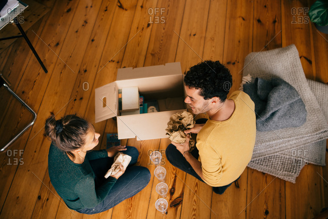 High angle view of couple removing glasses from box in living room at new home