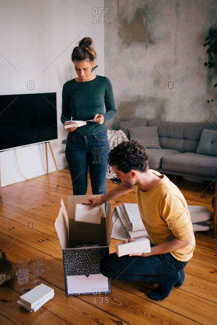 Couple removing novels from box in living room at new home