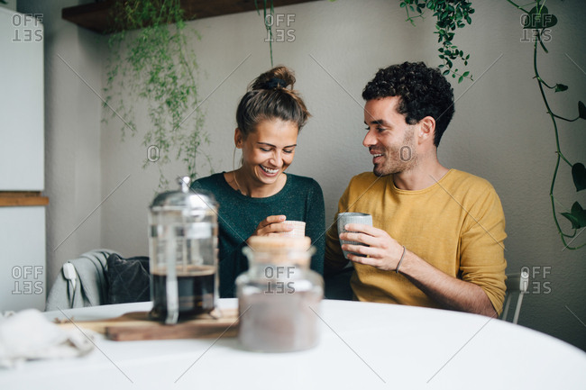 Smiling boyfriend and girlfriend having coffee at table in living room