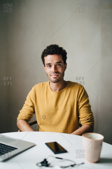 Portrait of confident mid adult man sitting at table against wall