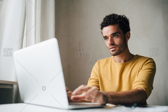 Mid adult man using laptop at home
