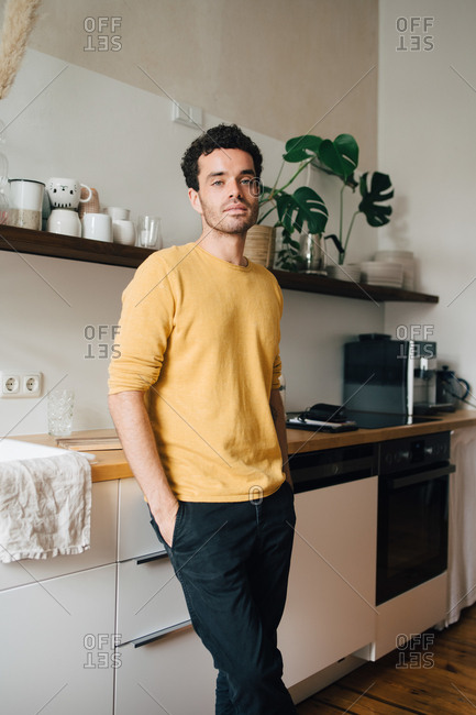 Portrait of confident mid adult man standing in kitchen at home