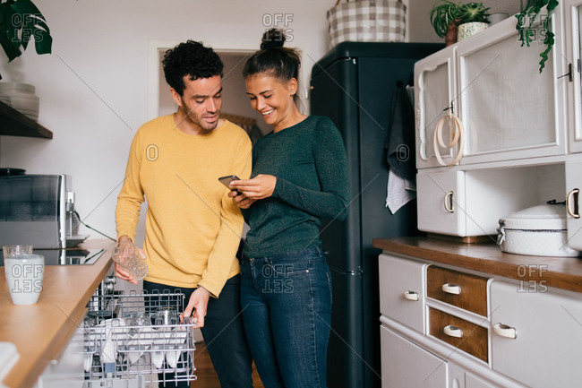 Woman smiling while showing smart phone to boyfriend while standing in kitchen