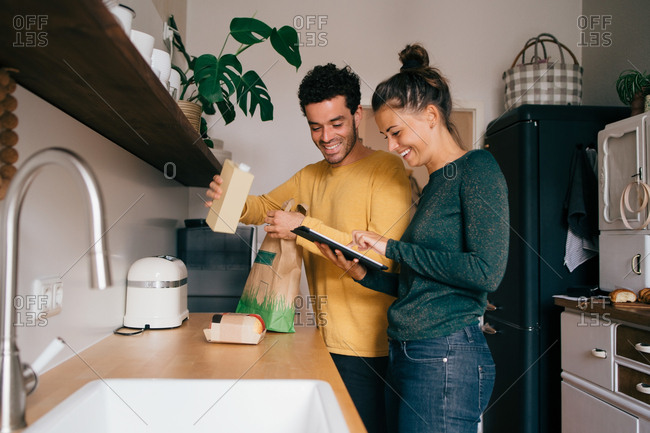 Smiling man removing food from bag while girlfriend showing digital tablet at kitchen counter