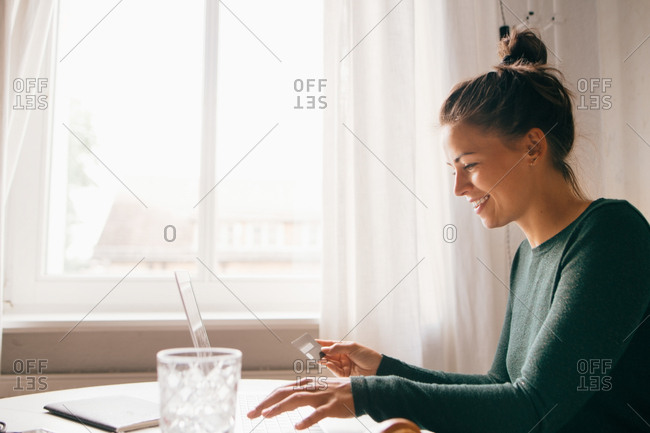 Side view of smiling woman with credit card using laptop in living room