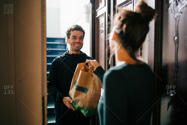 Smiling delivery man delivering bag to woman standing at doorway