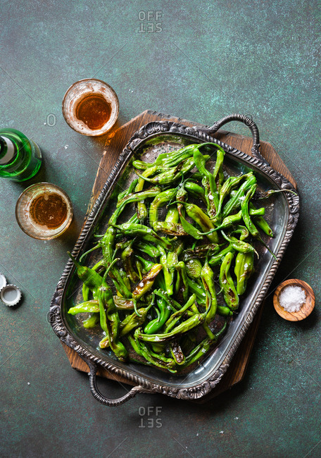 Top view of fried shishito peppers (padron peppers) on vintage metal tray with glasses of beer