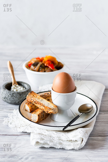 Boiled egg for breakfast, salt, toasted bread and roasted vegetables on side